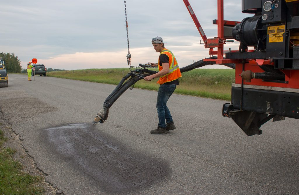 asphalt product being applied by spray patcher in alberta