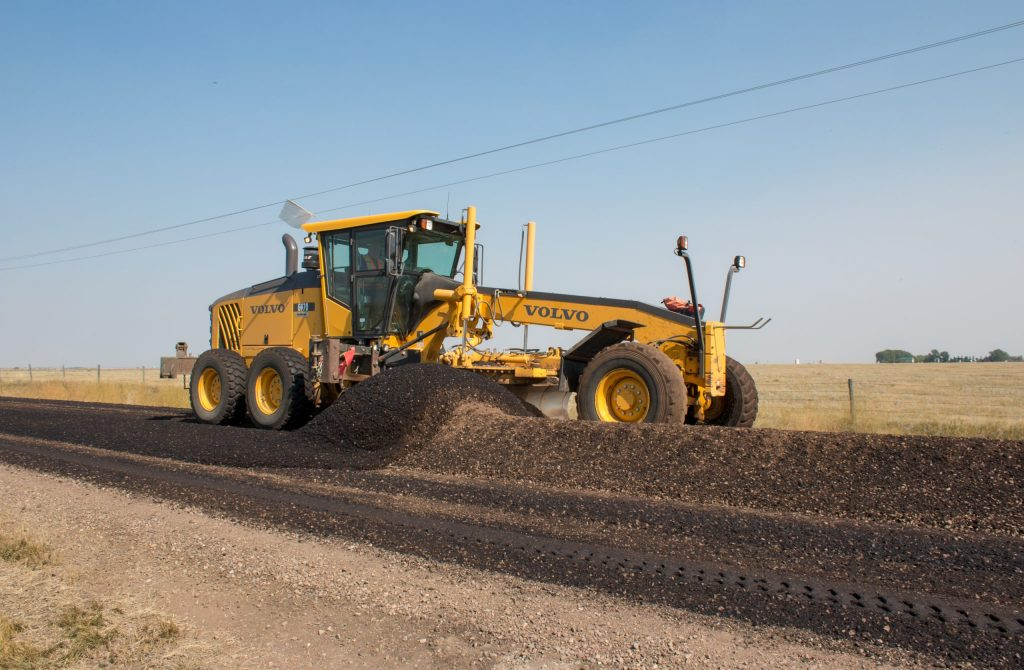 grader doing dust suppression and cold mix in alberta